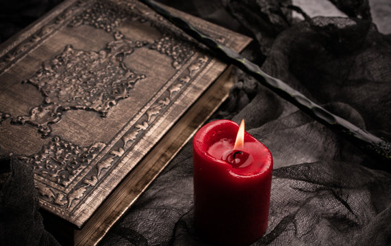 Old book with spells, red candle and magic wand on gray background with witch rag. Copy space for text