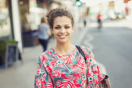 Portrait smiling young woman on urban street