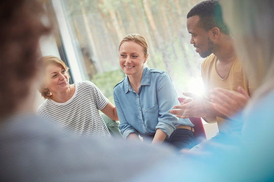 People clapping for woman in group therapy session