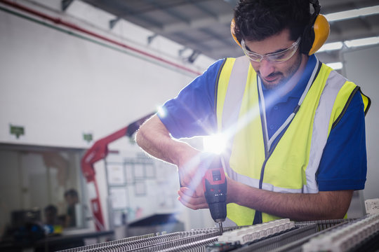 Male engineer with power drill assembling equipment in steel factory