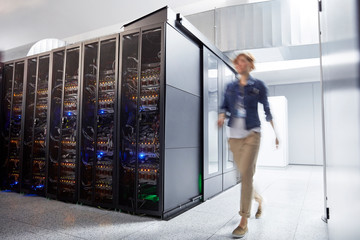 Female IT technician walking in server room