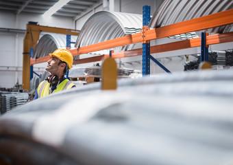 Male worker looking up in steel factory