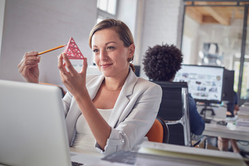 Smiling female design professional examining triangle prototype at laptop in office