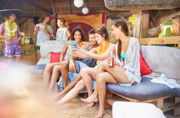 Young friends hanging out, drinking and taking selfie at summer poolside