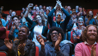 Excited audience clapping in dark room