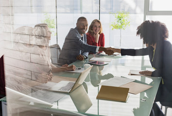 Businessman businesswoman handshaking across conference table in meeting
