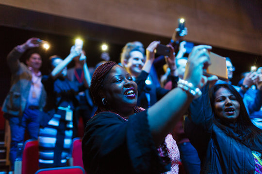 Smiling woman using camera phone in audience