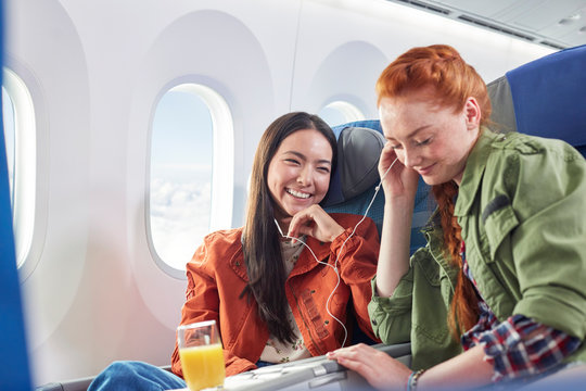 Young women friends sharing headphones, listening to music on airplane