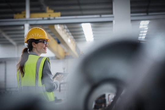 Confident female worker using digital tablet in steel factory