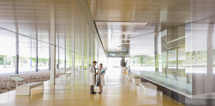 Scientists in lab coats talking in modern office lobby corridor
