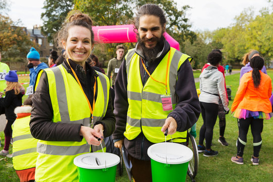 Portrait smiling volunteers donation buckets at charity run in park