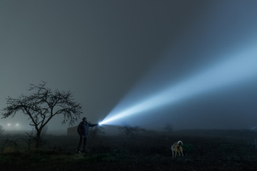 Man and dog exploring field at night, lightening with torch to sky at night.