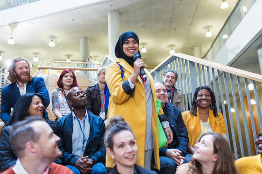 Smiling woman in hijab speaking with microphone in conference audience