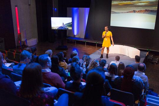 Female speaker on stage talking to audience