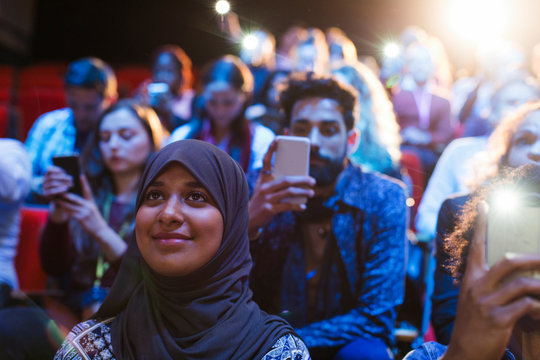 Smiling woman in hijab listening in audience