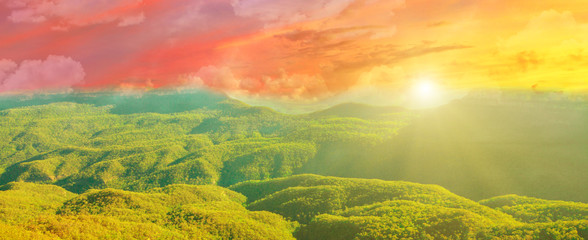 Banner panorama of amazing dramatic colorful sunset of fire with sun rays over Blue Mountains National Park landscape in New South Wales, Australia.
