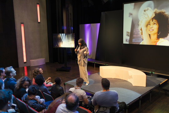 Female speaker in hijab on stage talking to audience