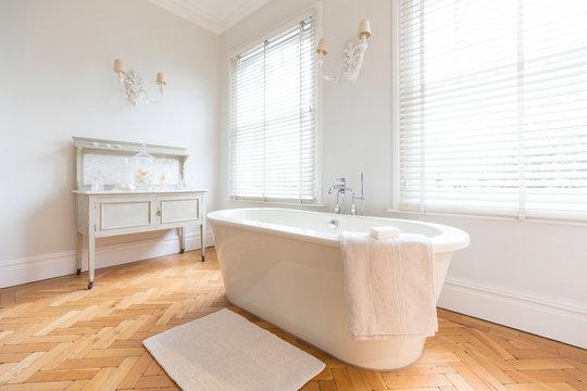 White, luxury home showcase interior bathroom soaking tub parquet hardwood floor