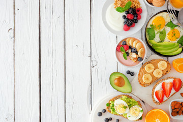 Healthy breakfast food side border. Table scene with fruit, yogurt, smoothie, nutritious toasts and...