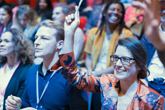 Smiling woman in conference audience raising hand