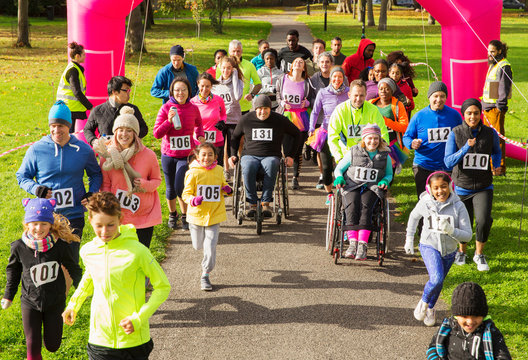 Crowd running at charity run in sunny park