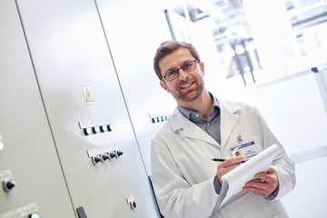 Portrait male technician in lab coat with clipboard in electrical control room