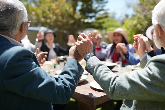 Active senior friends holding hands, praying at sunny garden party table