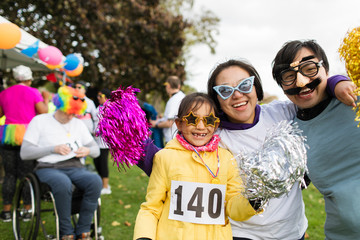 Portrait playful family wearing silly eyeglasses at charity run in park