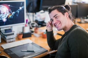Portrait smiling, confident male graphic designer working at desk
