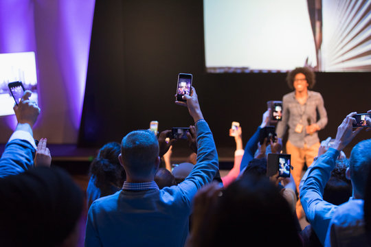 Audience members with smart phones videoing speaker on stage at conference