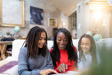 Smiling mother and daughters looking at photo album on sofa