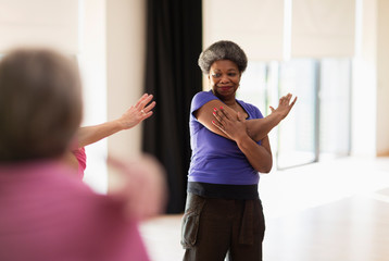 Smiling active senior stretching arm in exercise class