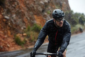Dedicated young man cycling on rainy road