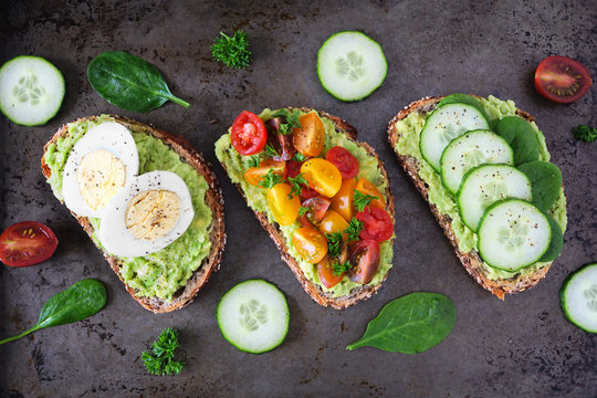 Healthy avocado toast assortment. Eggs, tomatoes and cucumber spinach. Flat lay over a dark background.