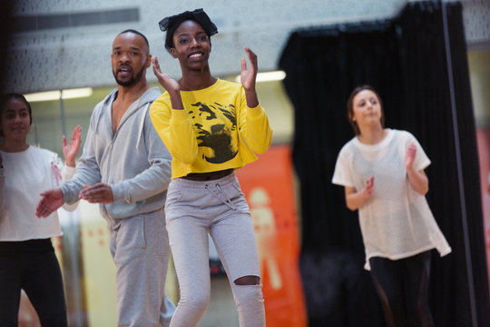 Smiling, enthusiastic teenage girl clapping, dancing in dance class studio