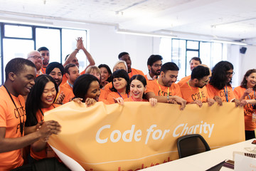 Hackers with banner coding for charity at hackathon Fotobehang