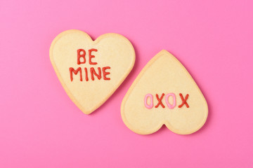 Valentines Day Concept: Two Heart Shaped sugar cookies on pink with sayings - Be Mine and XOXO.