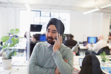 Serious Indian businessman in turban talking on smart phone in office Wall mural