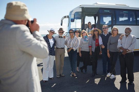 Active senior tourist friends posing for photograph outside tour bus