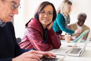 Portrait smiling, confident senior businesswoman using laptop in conference room meeting