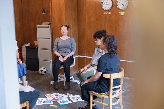 Serene, creative businesswomen meditating in circle, taking a break in meeting