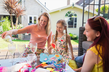 Lesbian couple enjoying white wine doing craft project daughter on patio