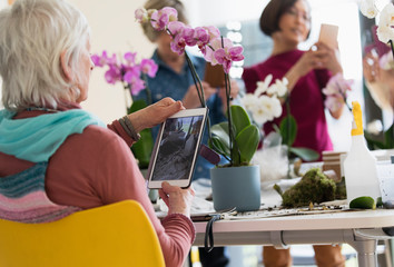 Active senior woman digital tablet photographing orchid in flower arranging class