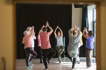 Active seniors exercising in circle, practicing yoga tree pose