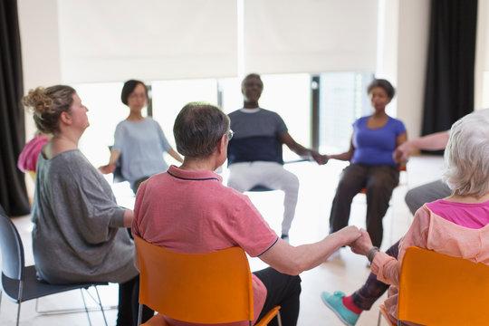 Serene active seniors holding hands, meditating in circle