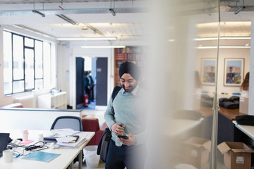 Indian businessman in turban using smart phone in office
