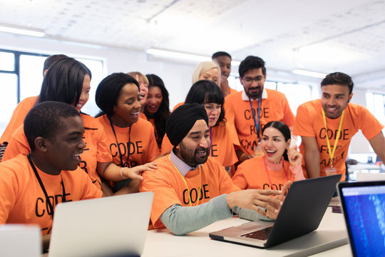Happy hackers at laptop coding for charity at hackathon