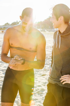 Male runner with fitness tracker checking wristwatch on sunny beach