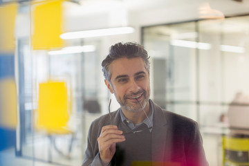 Confident, smiling creative businessman brainstorming in office Wall mural