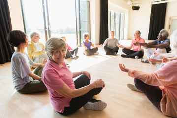 Portrait smiling active senior woman meditating in circle
